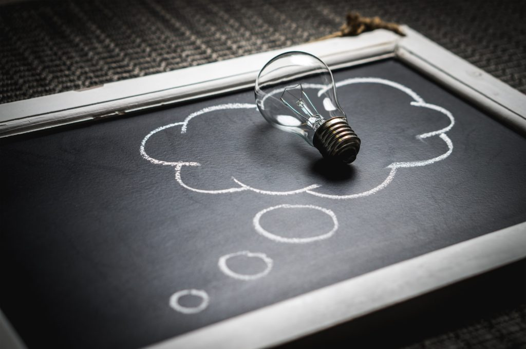 How to decide what business to start. Light bulb in a thought bubble that is drawn on a chalkboard